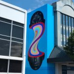 Murals of monochromatic figures pouring colorful fluids by Gina Kiel
